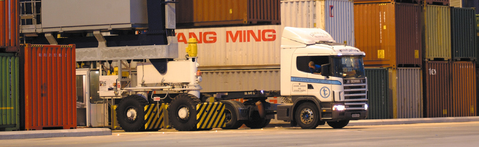 Haulage unit driver reversing between ISO shipping containers