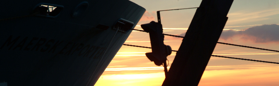 Bows of a cargo ship with the evening sky and mooring lines visible