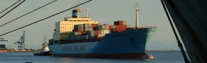 Container ship arriving in port helped by a tug