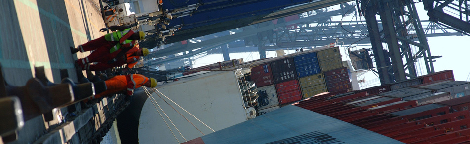 Dock workers beside loaded container ships
