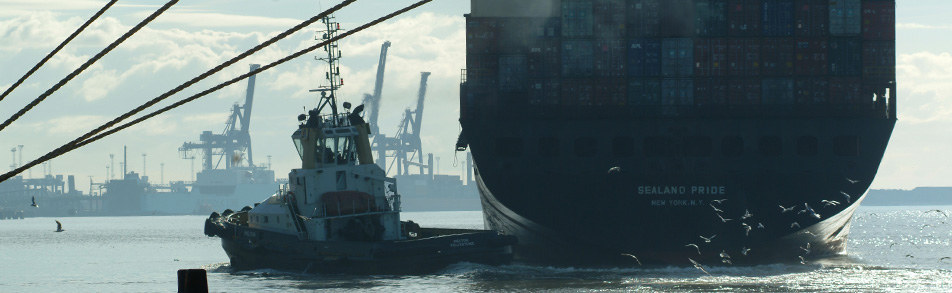 Cargo ship leaving the quay at Felixstowe port helped by a tug